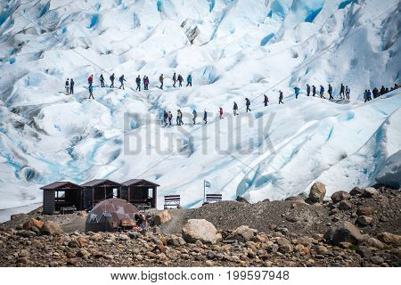 People walk on the slopes of the glacier. Tourists travel to glaciers.