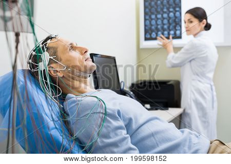 Best healthcare service. The focus being on a handsome middle-aged man undergoing electroencephalography while his doctor studying his CT scan results