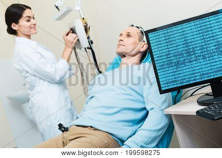 Crucial examination. Handsome young man lying with electrodes on his head while the doctor tuning electroencephalograph displaying brain waves on computer screen