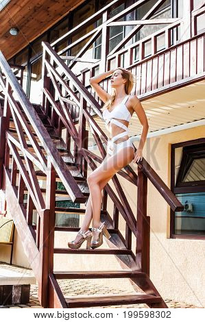 Beautiful woman wearing white fashion swimsuit monokini and high heeled sandals stay on stairs