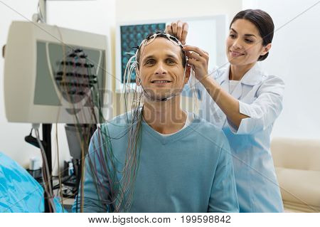 Professional skills. Beautiful young female doctor carefully removing the electrodes from her patients head, having finished the electroencephalography procedure