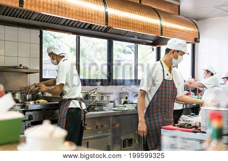 Bangkok, Thailand - August 13, 2017: Inside the restaurant with the open kitchen. Chefs cooking food quickly. To prepare the served to customers.