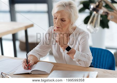 Taking notes. Thoughtful smart elderly woman looking at her notebook and thinking about her timetable while taking notes