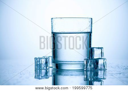 Glass of fresh water with ice cubes. Still water over blue background.