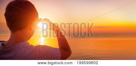 Happy little boy making heart with his hands over nature background. Joyful kid  showing heart from Hands with sunset inside. Vacation concept. Summer holidays. Tourism, vacation, wide banner format