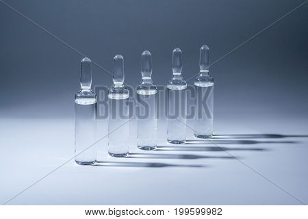 Row of ampules with medicine on blue background