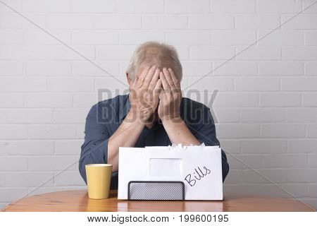 Mature man with his head in his hands with money worries