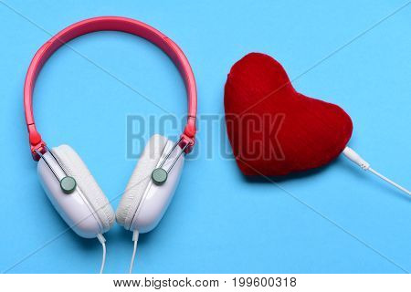 Music accessories and Valentines day concept. Modern and stylish earphones isolated on cyan background. Headset for music and heart shaped player. Headphones in white and red color with soft toy heart