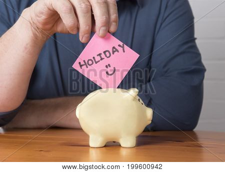 Unrecognisable man putting the word holiday into a money box