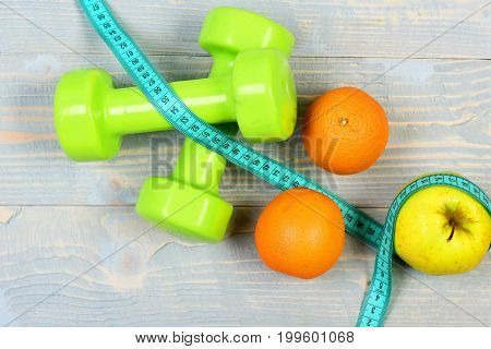 Slim Waist Concept, Dumbbells Weight With Measuring Tape And Fruits