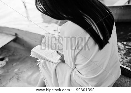 Close-up Photo Of Woman's Back While Reading A Book In A Boat. Black And White Photo.