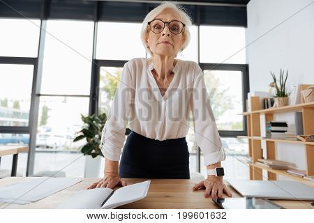 Strict boss. Serious intelligent senior woman wearing glasses and leaning on the table while preparing to start her speech