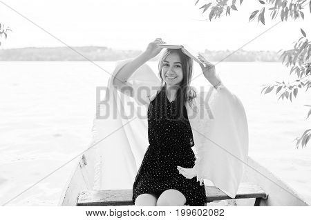 Portrait Of A Happy Woman In Polka Dot Dress Holding A Book Above Her Head While Sitting In An Old B