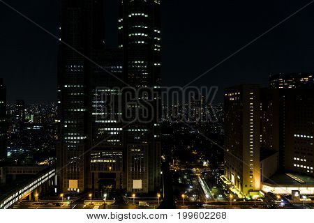 View on night Tokyo from high angle with massive buildings in front with colorful electricity lights and road