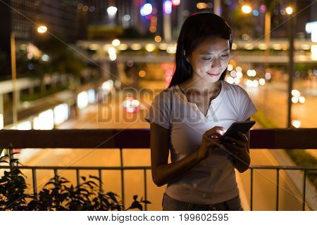 Woman using mobile phone in the city of Hong Kong at night