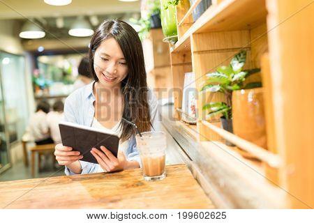 Woman using digital tablet computer in coffee shop