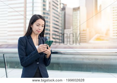 Business Woman sending sms on mobile phone in city