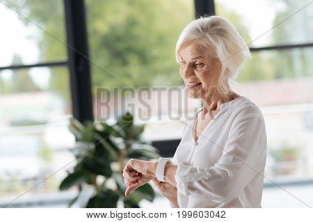 Time to go home. Cheerful nice elderly woman holding her watch and smiling while preparing to go home