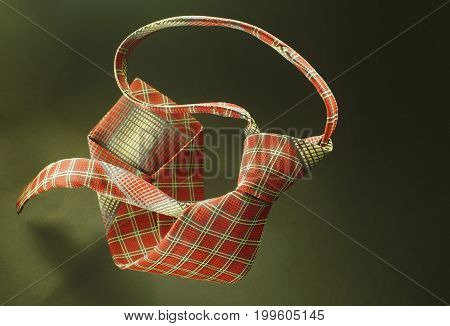 Red With Yellow Checkered Necktie On Green Fabric Background, Fashion Accessory Close Up