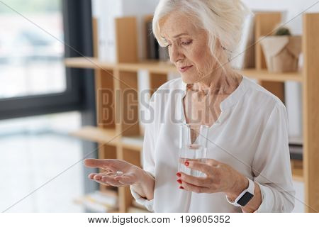 Daily dose. Nice cheerless aged woman holding a palm with the pill and looking at it while having a glass of water in her hands