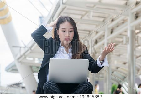 Young business woman working with laptop looking laptop notebook with shocked negative stress posture.