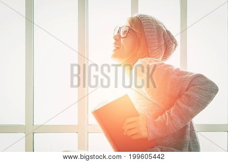 Young beautiful woman is happy with reading the book at home side of window in the room alone