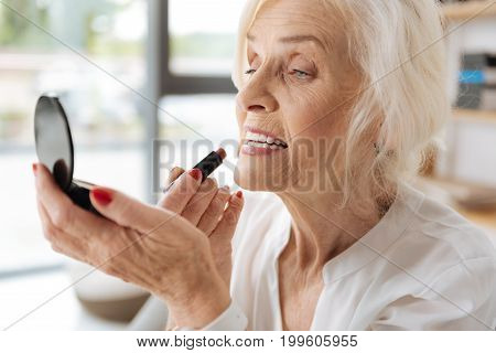 Staying beautiful. Nice positive senior woman holding a lipstick and putting on makeup while looking at her face refection