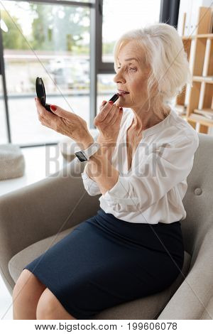 Looking great. Delighted good looking senior woman putting on some lipstick and looking into the mirror while sitting in the armchair