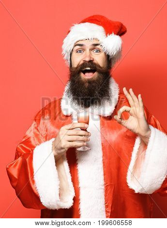 handsome bearded santa claus man with long beard on smiling face holding glass of alcoholic shot in christmas or xmas sweater and new year hat and showing ok on red studio background