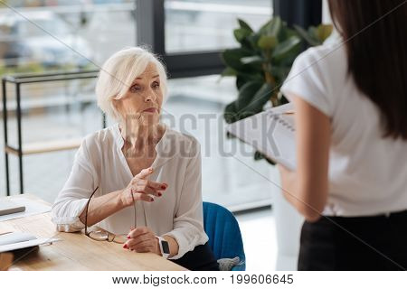 Experienced businesswoman. Nice professional modern businesswoman looking at her secretary and giving her instructions while being in charge