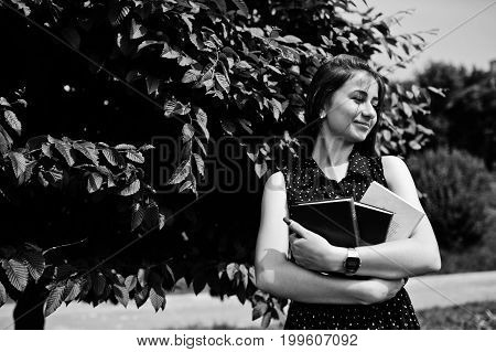 Portrait Of A Shy Young Woman In Black Polka Dot Dress Holding Books In The Park. Black And White Ph