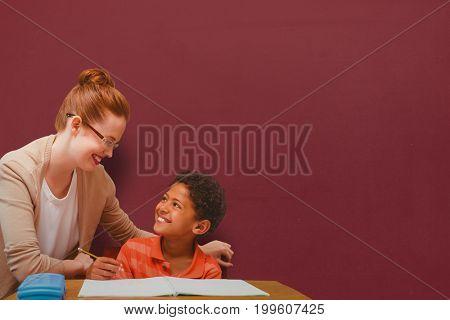Teacher helping pupil against chalkboard