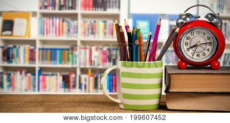 Books with alarm clock by colored pencils in mug on table against various books on shelf in library