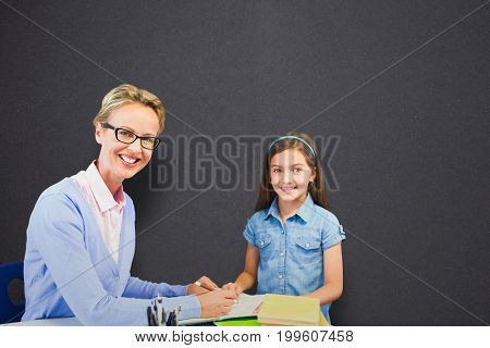 Portrait of teacher with student writing on book against black chalkboard