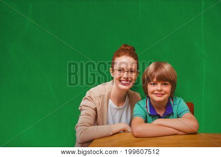 Happy pupil and teacher against blackboard with copy space on wooden board