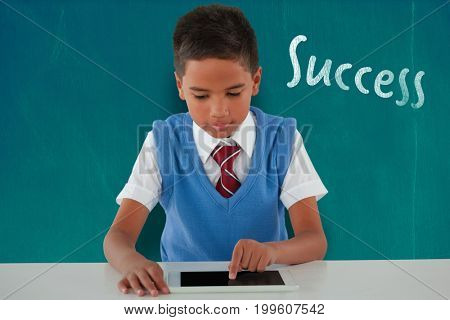 Schoolboy using digital tablet at table against blackboard with copy space on wooden board
