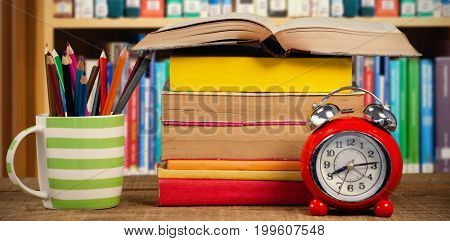 Stack of books by mug with colored pencils and alarm clock on table against multi colored books on shelf in library