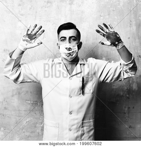 Doctor in latex gloves and surgical mask with hands up. Surgeon with hands in blood and confident sight. Treatment and ambulance services concept. Man in laboratory coat on beige wall background.