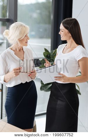 Work issues. Smart delighted female colleagues looking at each other and talking while discussing work