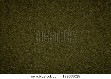 Texture of old dark green paper closeup. Structure of a dense olive cardboard. The background.