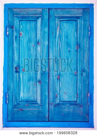 Blue painted closed wooden window shutters. Green turquoise painted wooden window shutters. Architectural detail