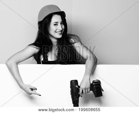 pretty cute sexy builder girl or smiling brunette woman in uniform and hard hat or helmet holding electric screwdriver on colorful studio backgroundcopy space