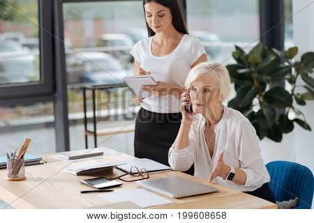 Business call. Serious intelligent pleasant woman sitting at the table and having a phone conversation while discussing business