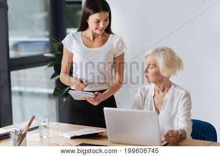 Professional worker. Professional chief executive officer sitting at the table and looking at the notes of her personal assistant while working on the laptop