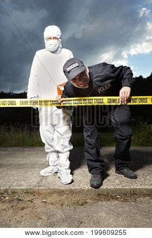 Police man securing place of crime with criminologist technician