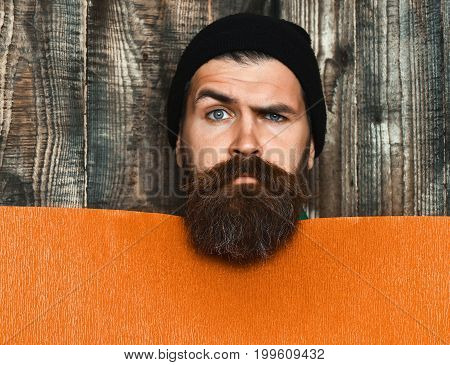 Bearded man long beard. Brutal caucasian serious unshaven hipster in black hat with orange paper sheet on grey wooden vintage studio background copy space
