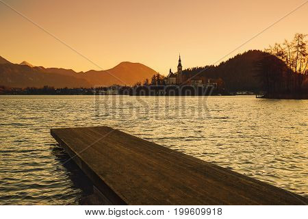 Amazing view on Bled Lake on sunrise with wooden pier. View on Island with Catholic Church. November morning on the lake at dawn. Autumn in Slovenia Europe.