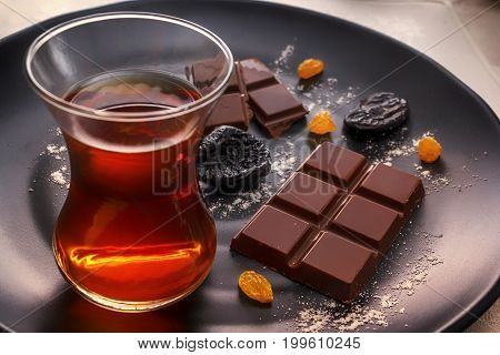 Chocolate, prunes, raisins and tea in a glass on a black plate. Soft light