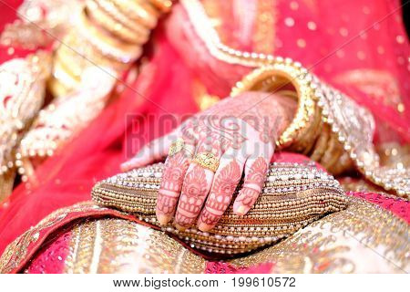 Close-up shoot of indian bride wearing elegant bangles, jewelry and rings in hand at wedding.