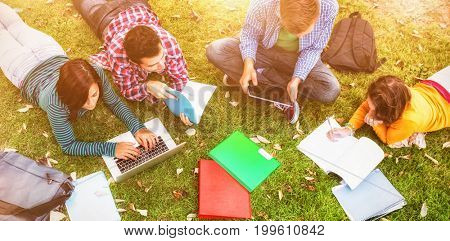 College students using laptop while doing homework at park